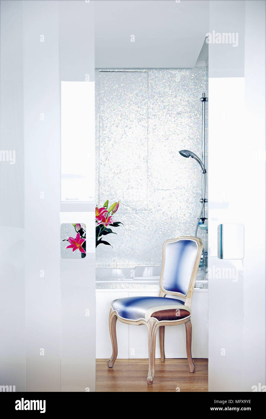 Period style chair in front of bathtub with shower over bath Stock ...
