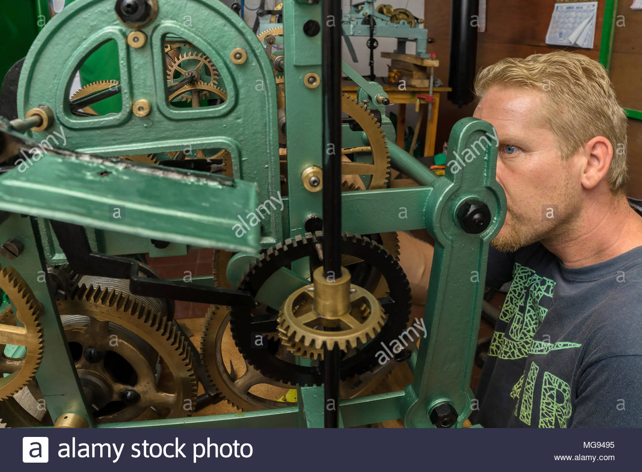 Clock Repair Shop: Blond man working on a 1926 German-made church clock from Belen, Nicaragua. Stock Photo