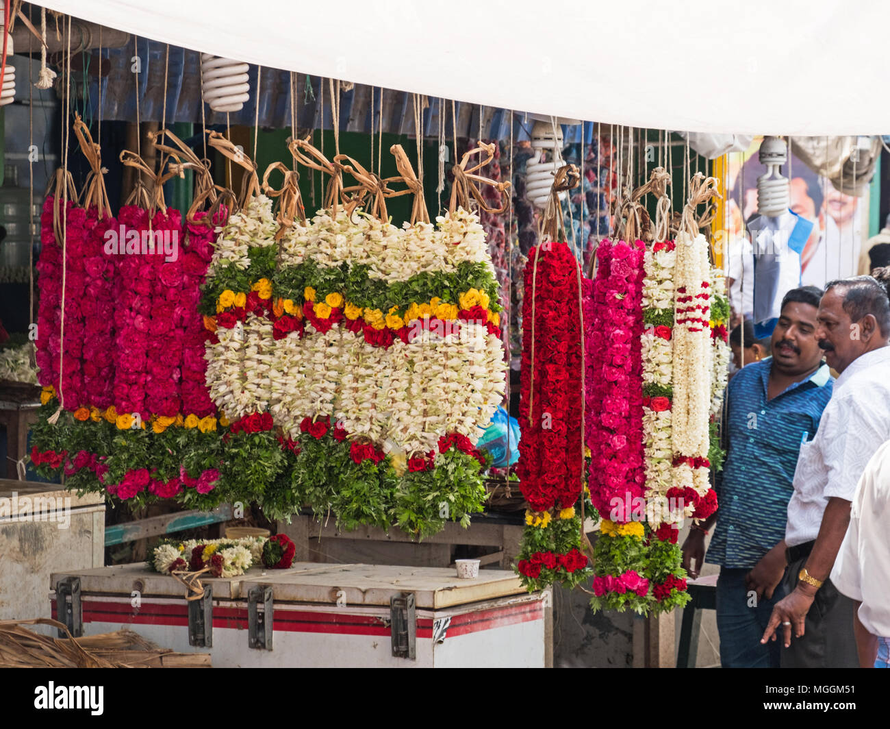 Madurai, India - March 11, 2018: Prospective customers examining garlands for sale in a flower market - Stock Image