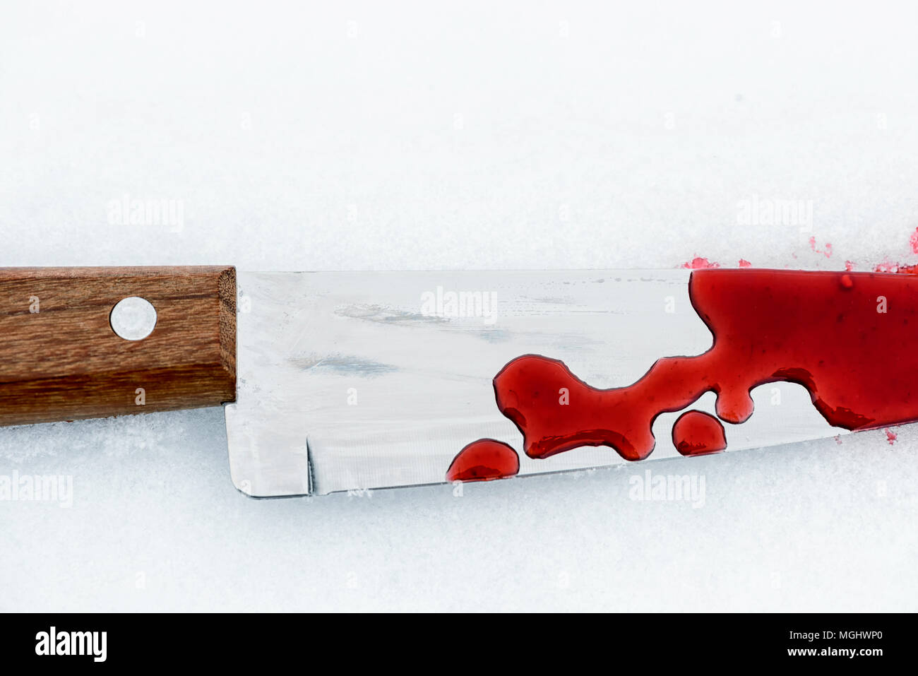 Sharp metal kitchen knife edge used as a violent murder weapon with blood drops on a white snow background. Blade covered in violence with copy space  - Stock Image