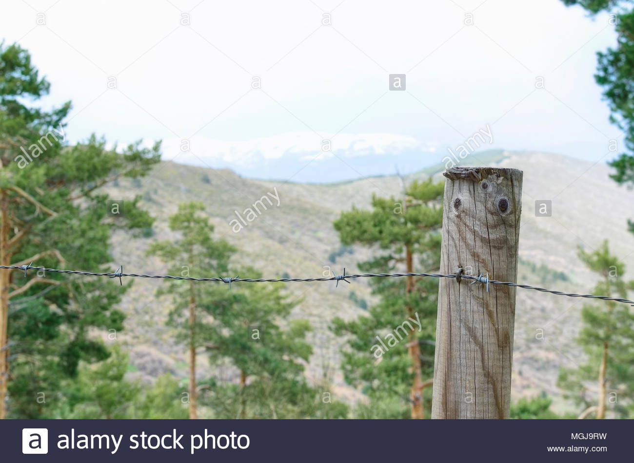 Weather In Guadarrama Mountain Range Madrid Spain Forefront Of Barbed Wire Mountain Fence Wintry Day In Spring Season