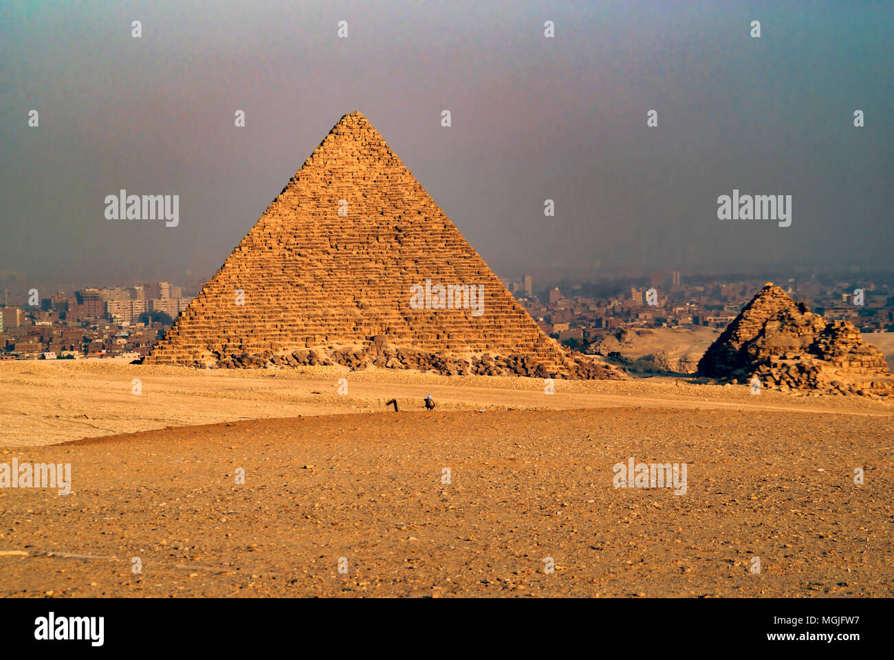 Pyramid of Mycerinus (Menkaure) and the three small Queen's Pyramids. Cairo, Egypt in the background. - Stock Image