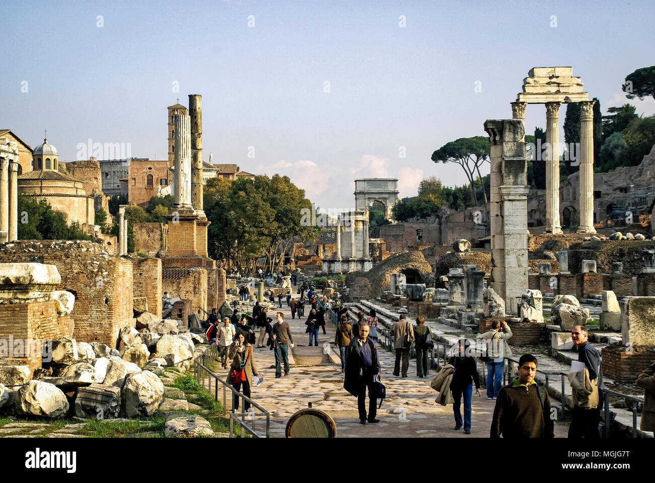 Tourists and business people stroll through the Roman Forum. You can see the Arch of Titus and the Temple of Castor on the right. Rome, Italy - Stock Image