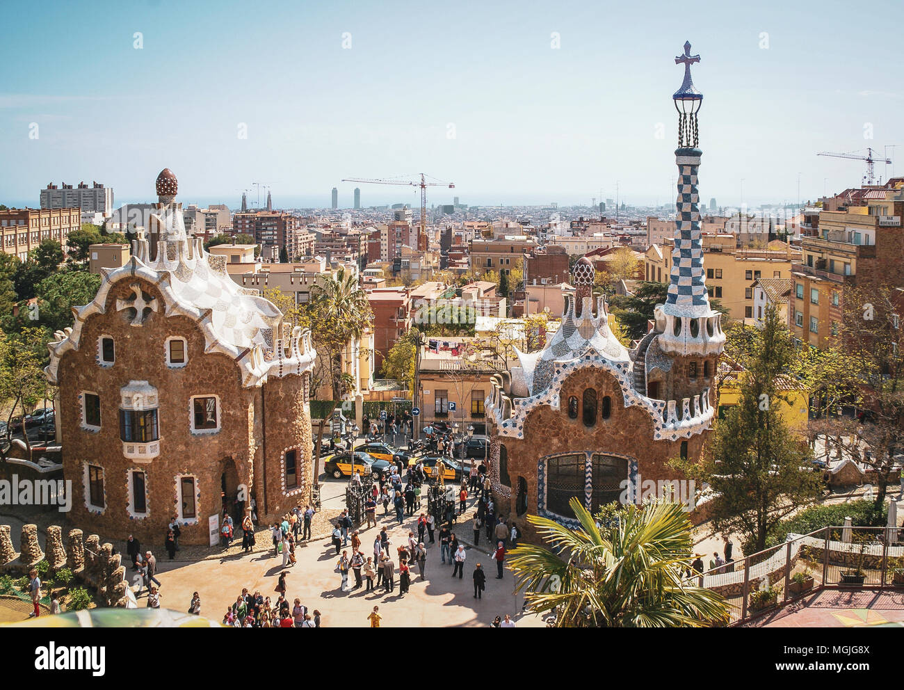 Fantasy houses by Gaudi at the entrance to Parc Guell. Barcelona, Spain. Visitors from all over the world. Urban Barcelona in the distance. - Stock Image