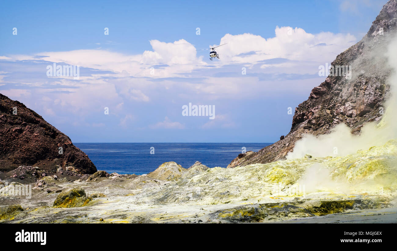 A helicopter coming in to land in the crater. White Island / Whakaarian volcano, New Zealand - Stock Image