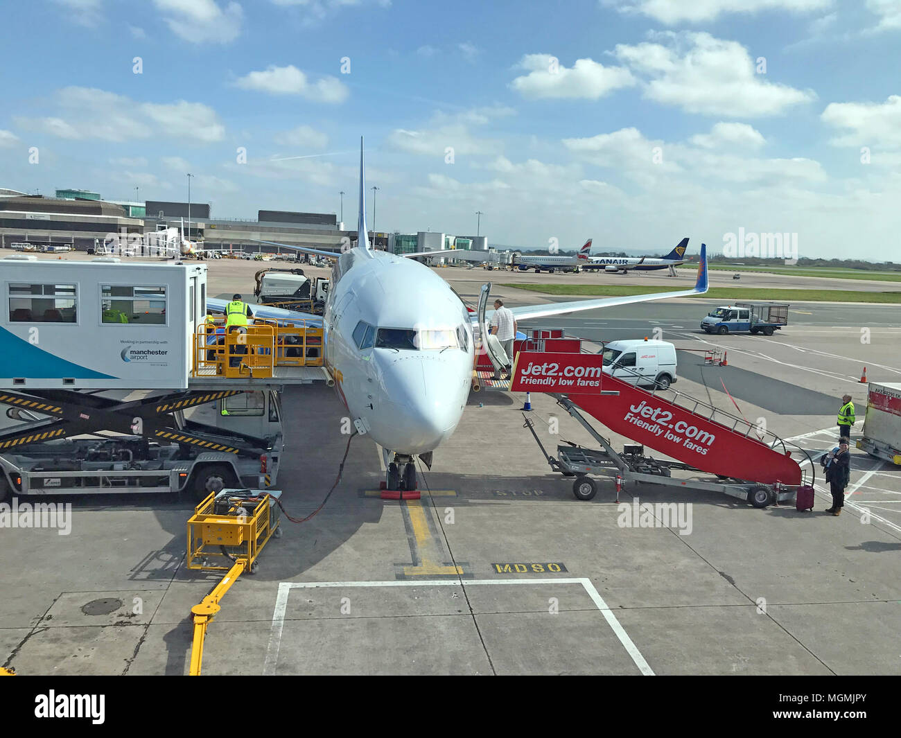 GoTonySmith,holiday,flight,apron,aircraft,at,Ringway,airport,International,refueling,at gate,gate,loading,boarding,Friendly Low Fares,travel,transportation,white,base,bases,jet,jets,ATOL,ABTA,sunny,spring,summer,stairs,load,catering,ground crew,crew,ground,stand,parked,container,containers,luggage