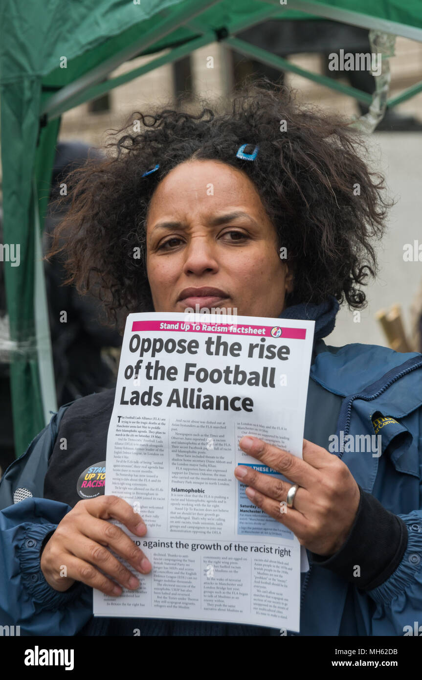London, UK. 30th April 2018.  A Stand Up to Racism supporter holds up their factsheet about the right-wing Footbal Lads Alliance at the protest in support of the petition calling for an end to the deportations of migrants in the 'Windrush generation' who arrived in Britain between 1948 and 1971. It calls on the government to change the burden of proof which means they are now required to prove their right to remain, and to provide compensation for any loss and hurt.. Credit: Peter Marshall/Alamy Live News - Stock Image
