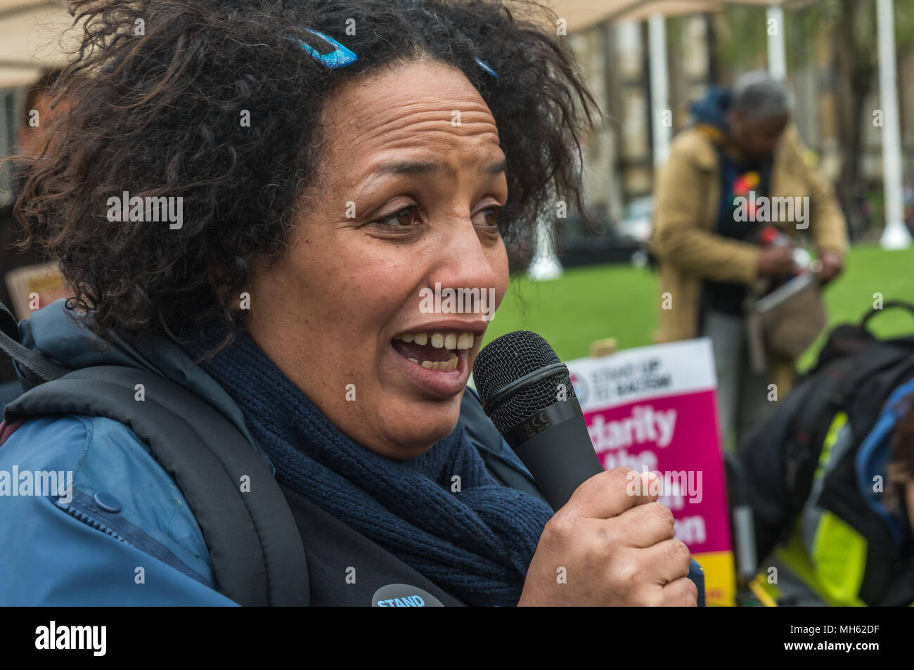 London, UK. 30th April 2018.  A London Stand Up To Racism supporter speaks at the protest in support of the petition calling for an end to the deportations of migrants in the 'Windrush generation' who arrived in Britain between 1948 and 1971. It calls on the government to change the burden of proof which means they are now required to prove their right to remain, and to provide compensation for any loss and hurt.. re for many years, paying taxes and raising families h Credit: Peter Marshall/Alamy Live News - Stock Image