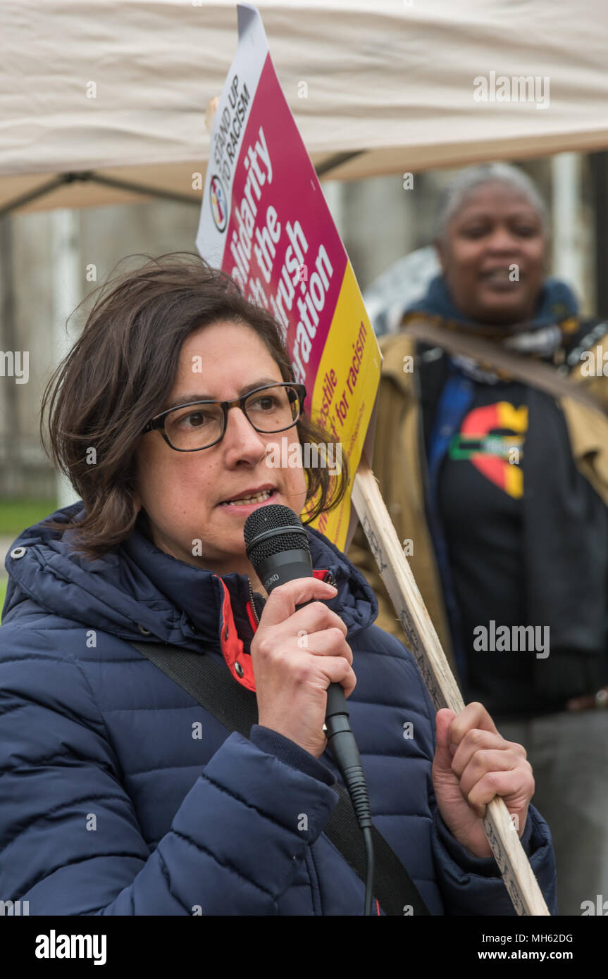 London, UK. 30th April 2018. A medical professional speaks about the huge contribution made by migrant workers to the NHS at the protest in support of the petition calling for an end to the deportations of migrants in the 'Windrush generation' who arrived in Britain between 1948 and 1971. It calls on the government to change the burden of proof which means they are now required to prove their right to remain, and to provide compensation for any loss and hurt.. re for Credit: Peter Marshall/Alamy Live News - Stock Image