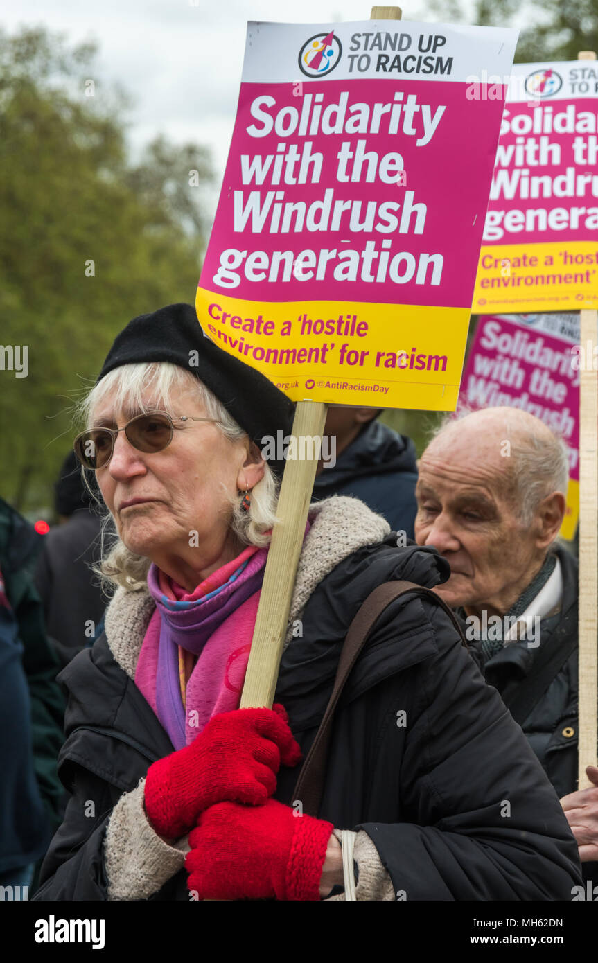 London, UK. 30th April 2018.  A woman holds a placard at the protest in support of the petition calling for an end to the deportations of migrants in the 'Windrush generation' who arrived in Britain between 1948 and 1971. It calls on the government to change the burden of proof which means they are now required to prove their right to remain, and to provide compensation for any loss and hurt.. re for many years, paying taxes and raising families here and have long reg Credit: Peter Marshall/Alamy Live News - Stock Image