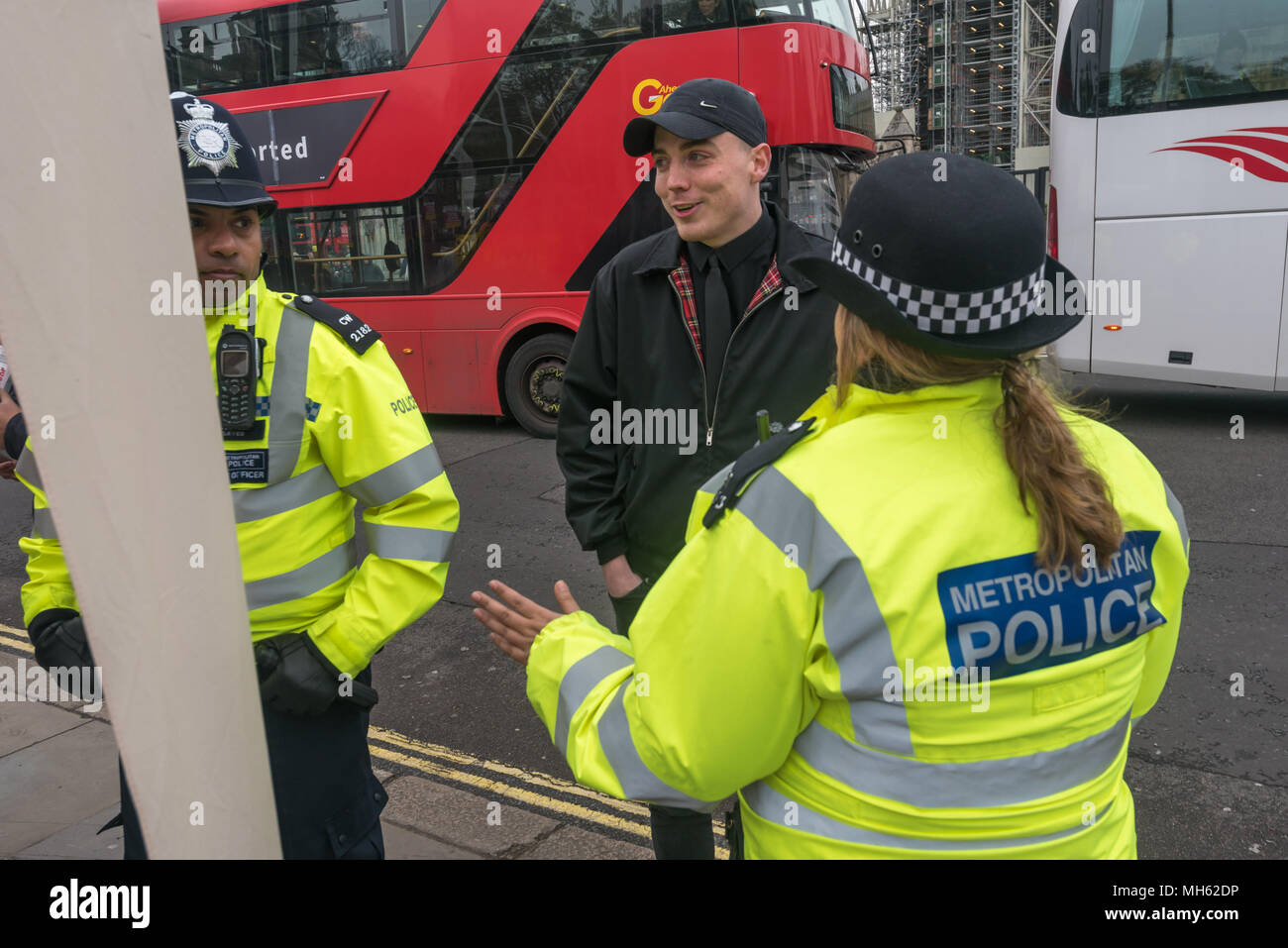 London, UK. 30th April 2018.  Police ask a man who has come to cause trouble to leave the protest in support of the petition calling for an end to the deportations of migrants in the 'Windrush generation' who arrived in Britain between 1948 and 1971. It calls on the government to change the burden of proof which means they are now required to prove their right to remain, and to provide compensation for any loss and hurt.. re for many years, paying taxes and raising fa Credit: Peter Marshall/Alamy Live News - Stock Image