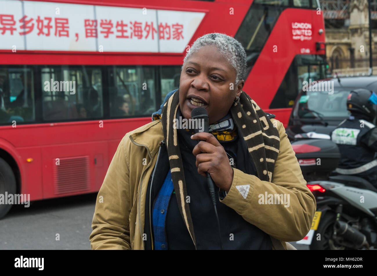 London, UK. 30th April 2018.  A Londoner speaks about the Grenfell fire and the failures of local and national governemnt it has exposed at the protest in support of the petition calling for an end to the deportations of migrants in the 'Windrush generation' who arrived in Britain between 1948 and 1971. It calls on the government to change the burden of proof which means they are now required to prove their right to remain, and to provide compensation for any loss and hurt.. Most of those who have been deported, threatened with deportation or refused entry after visiting families abroad have w - Stock Image