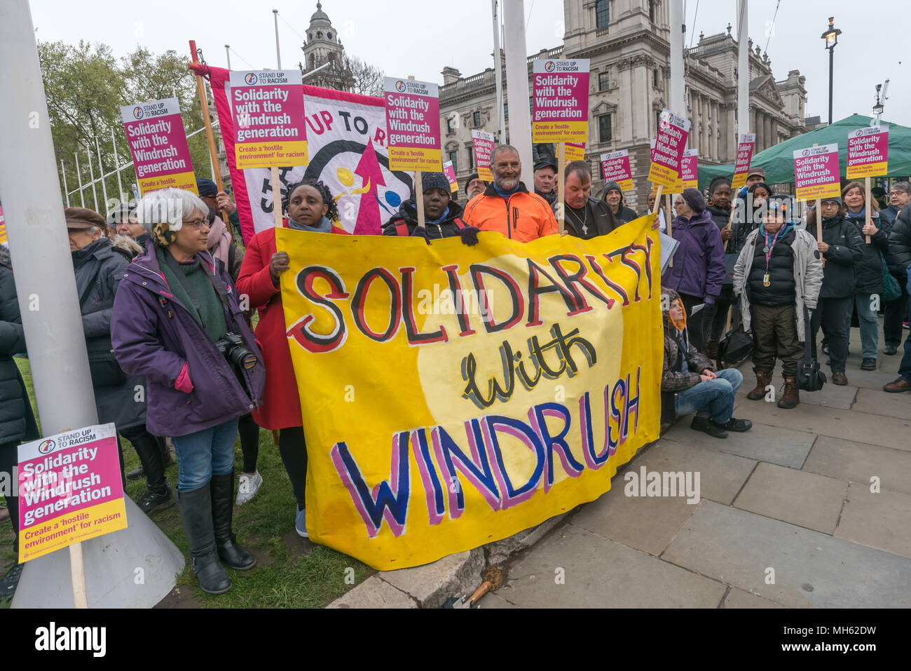 London, UK. 30th April 2018.  People hold the 'Solidarity With Windrush' banner at the protest in support of the petition calling for an end to the deportations of migrants in the 'Windrush generation' who arrived in Britain between 1948 and 1971. It calls on the government to change the burden of proof which means they are now required to prove their right to remain, and to provide compensation for any loss and hurt.. re for many years, paying taxes and raising famil Credit: Peter Marshall/Alamy Live News - Stock Image