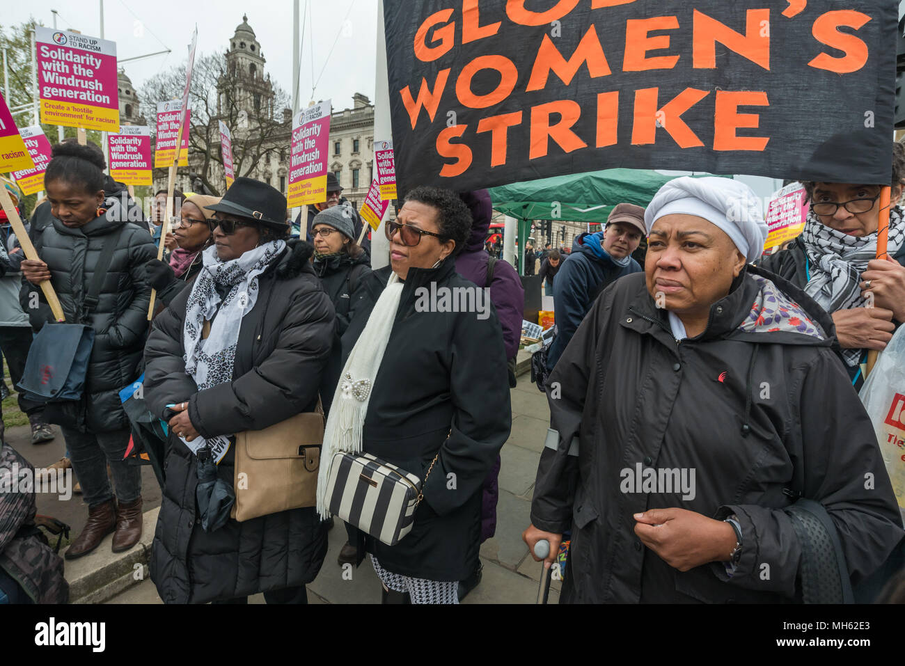 London, UK. 30th April 2018.  Women stand in fornt of the Global Women's Strike banner at the protest in support of the petition calling for an end to the deportations of migrants in the 'Windrush generation' who arrived in Britain between 1948 and 1971. It calls on the government to change the burden of proof which means they are now required to prove their right to remain, and to provide compensation for any loss and hurt.. re for many years, paying taxes and raisin Credit: Peter Marshall/Alamy Live News - Stock Image