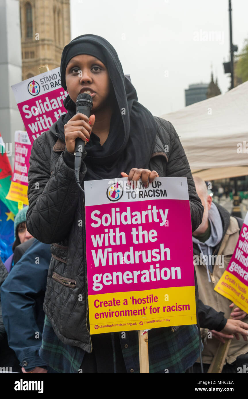 London, UK. 30th April 2018.  A Muslim activist from Stand Up to Racism speaks at the protest in support of the petition calling for an end to the deportations of migrants in the 'Windrush generation' who arrived in Britain between 1948 and 1971. It calls on the government to change the burden of proof which means they are now required to prove their right to remain, and to provide compensation for any loss and hurt.. re for many years, paying taxes and raising famili Credit: Peter Marshall/Alamy Live News - Stock Image