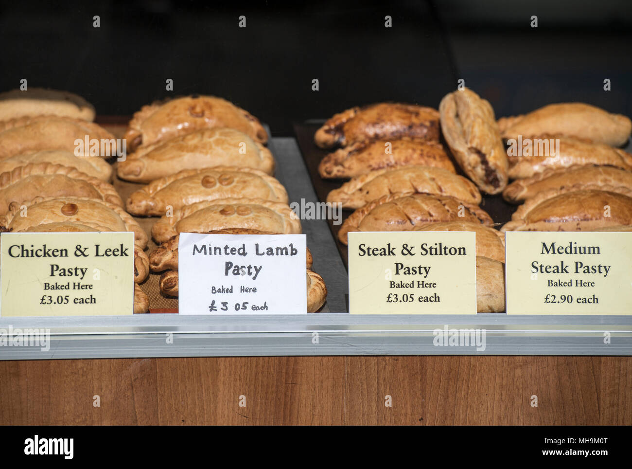 Cornish pasties on display in a bakery shop window in St Ives, Cornwall, England, UK - Stock Image
