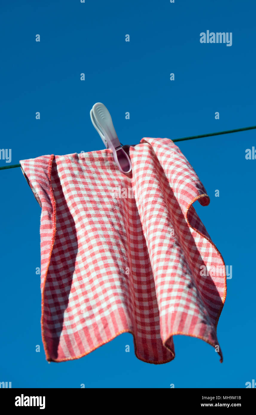 Red and white tea towel drying on a washing line - Stock Image