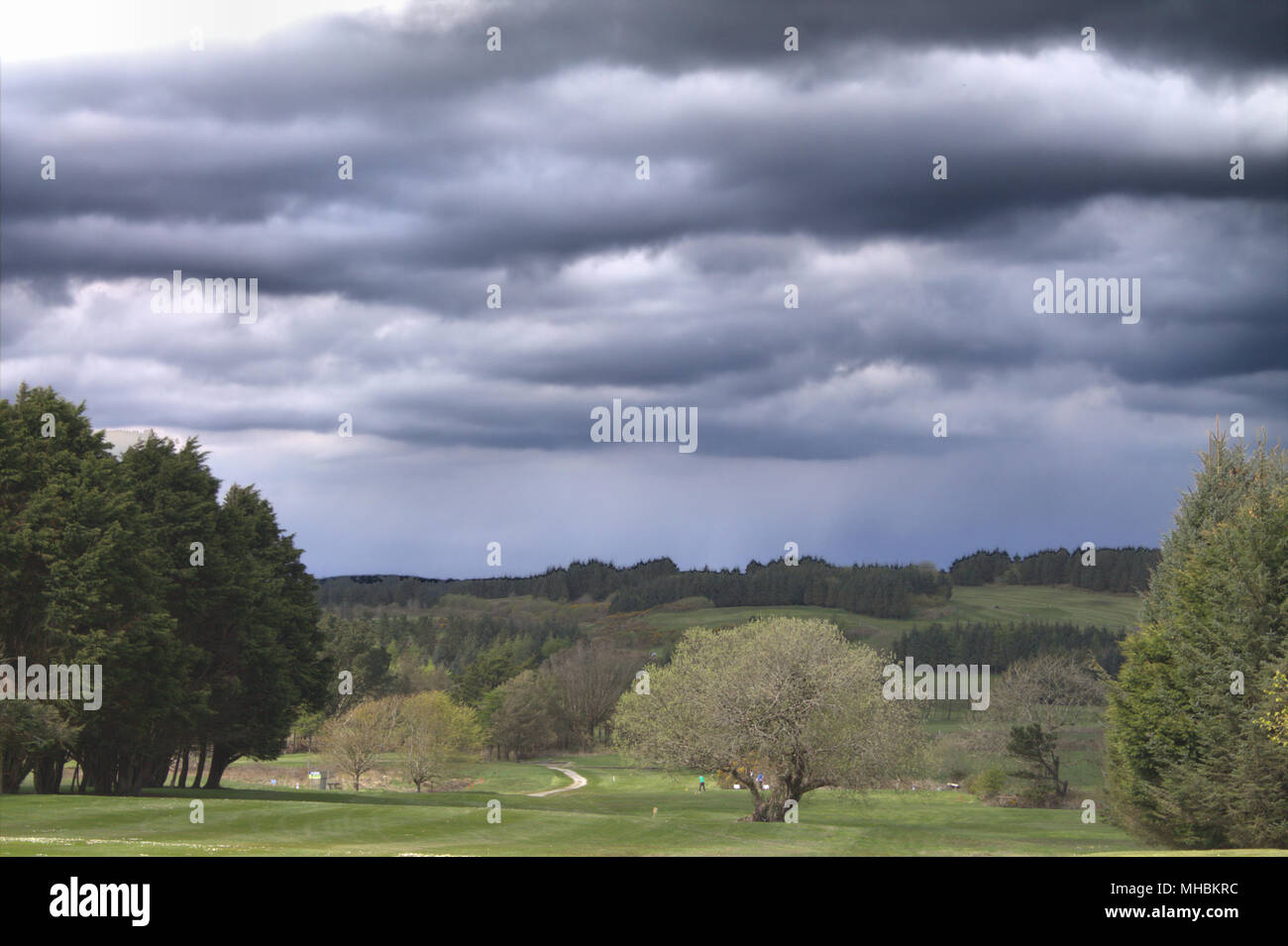 thunderstorm-clouds-gathering-over-players-out-on-a-golf-course-MHBKRC.jpg