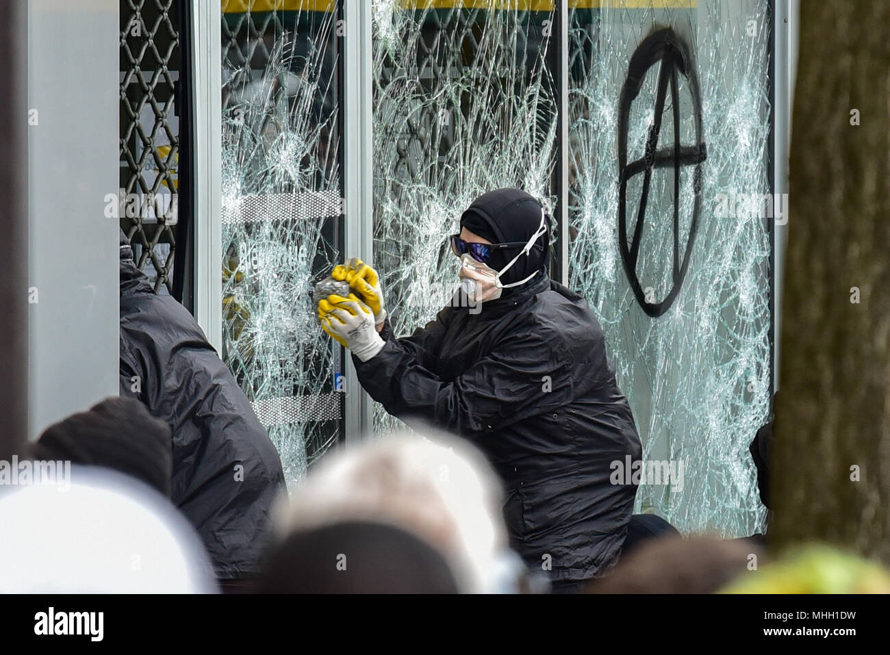 Paris, France. 1st May 2018. Paris police clash with protesters as demonstrations turn violent. PICTURED: A 'Black Bloc' protester smashes a shop window. Credit: Peter Manning/Alamy Live News - Stock Image