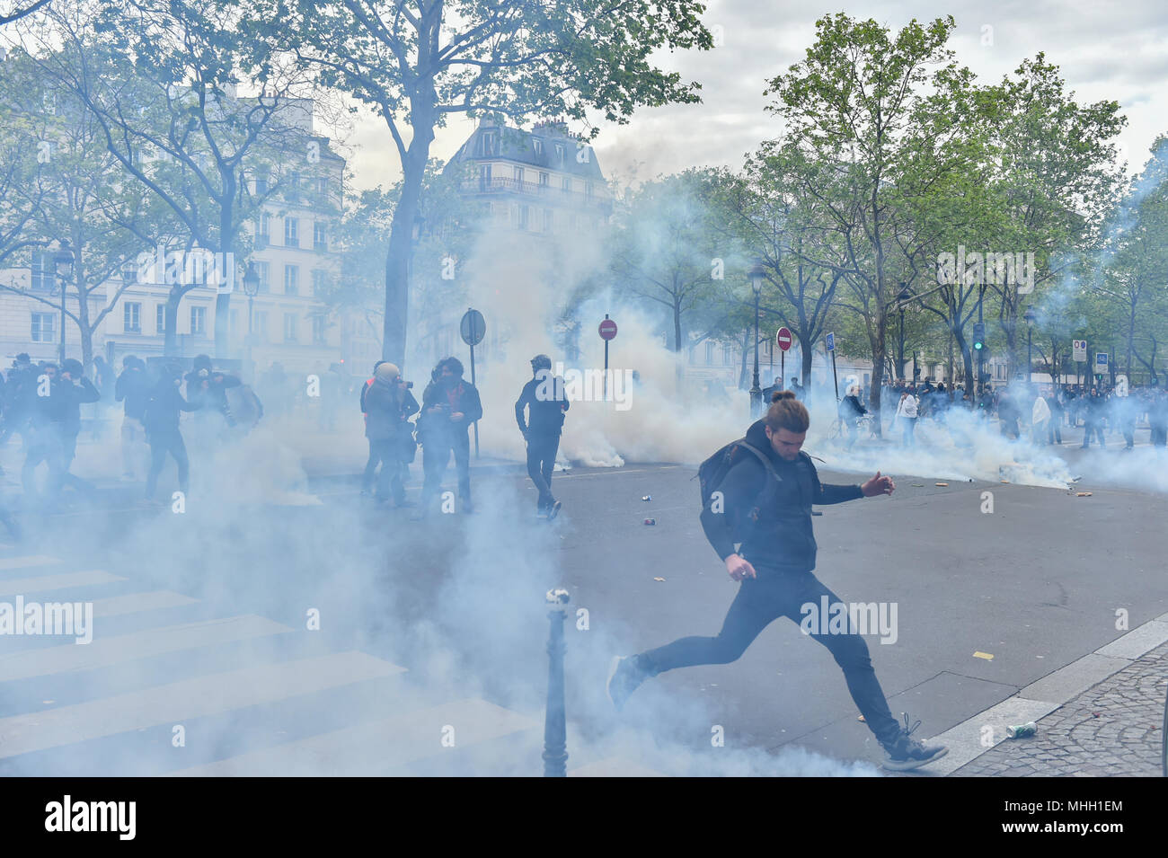 Paris, France. 1st May 2018. Paris police clash with protesters as demonstrations turn violent. PICTURED: A protester kicks a tear gas canister away from other protesters. Credit: Peter Manning/Alamy Live News - Stock Image