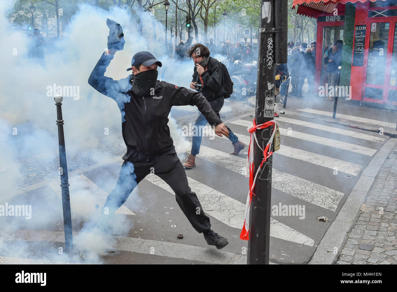 Paris, France. 1st May 2018. Paris police clash with protesters as demonstrations turn violent. PICTURED: A protester throws a tear gas canister back towards police. Credit: Peter Manning/Alamy Live News - Stock Image