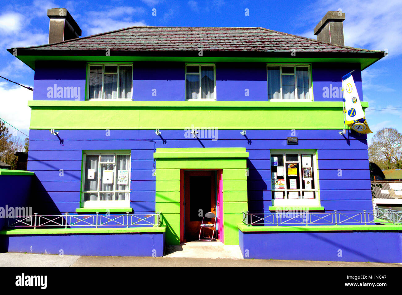 brightly-coloured-or-colored-vivid-blue-and-green-brick-built-building-a-converted-domestic-house-standing-out-in-the-midday-sun-MHNC47.jpg