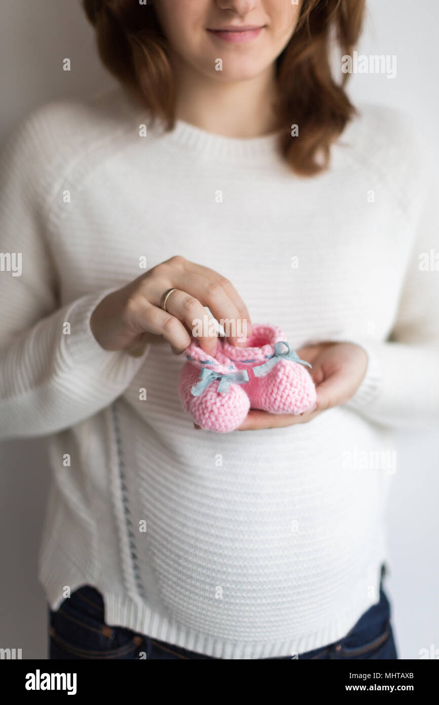 child fashion, pregnancy, expectation concept. close up of decorative baby bootees in delicate arms of future mother, they was sewed of pink yarn and embelished with blue ribbons - Stock Image