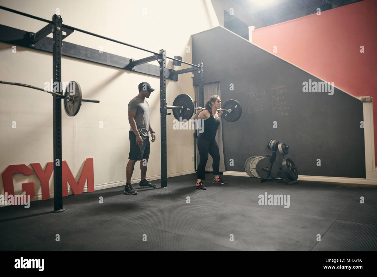 Woman in gym weightlifting using barbell - Stock Image