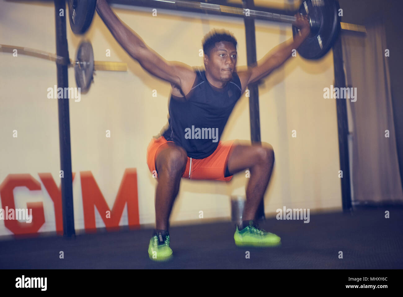 Man in gym weightlifting using barbell, defocused - Stock Image