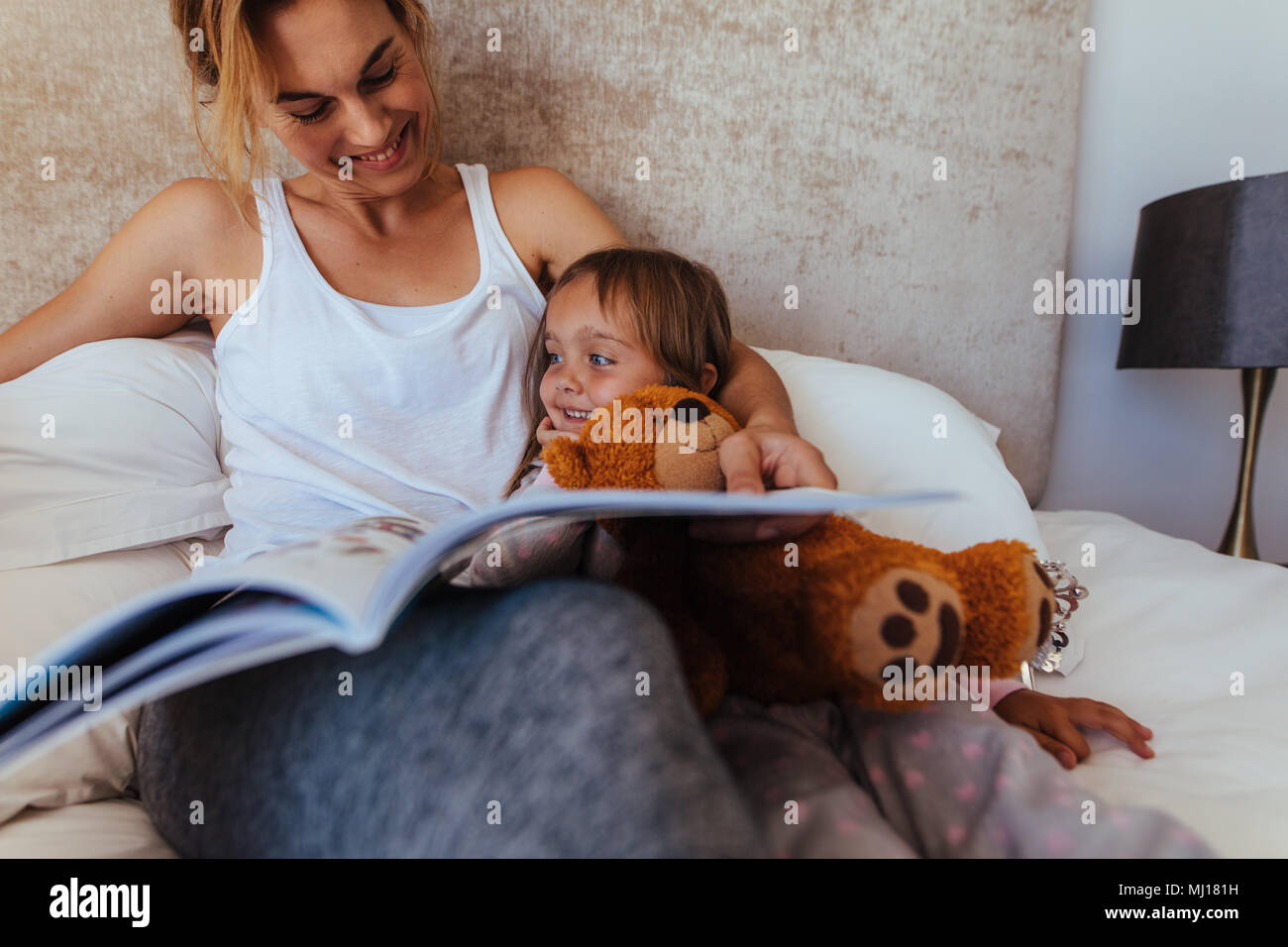 Bedtime story stock photos bedtime story stock images alamy happy family reading bedtime story in bed woman looking at her daughter and smiling while sciox Gallery