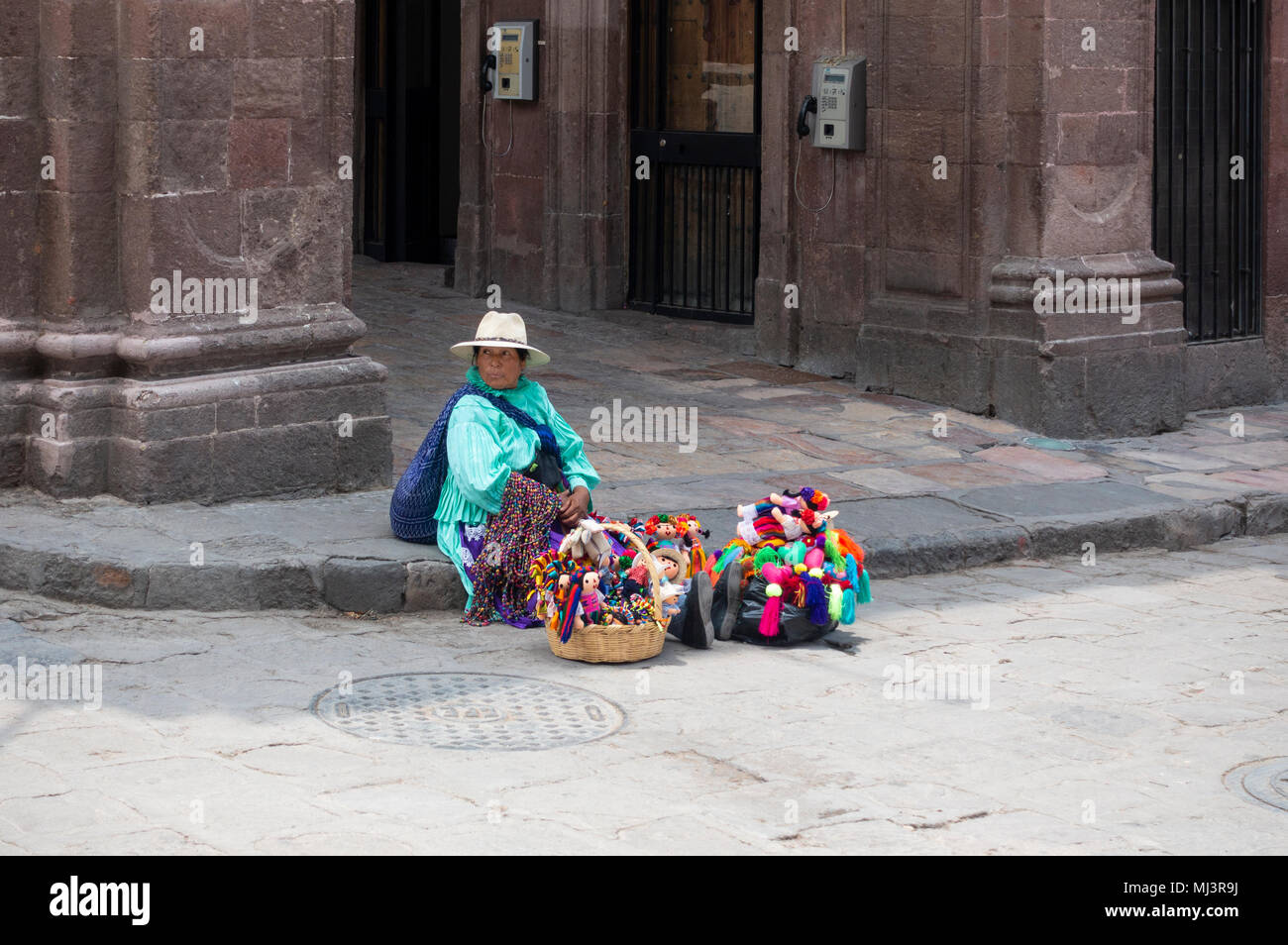 Indian woman in straw hat selling Mexican children's dolls - Stock Image