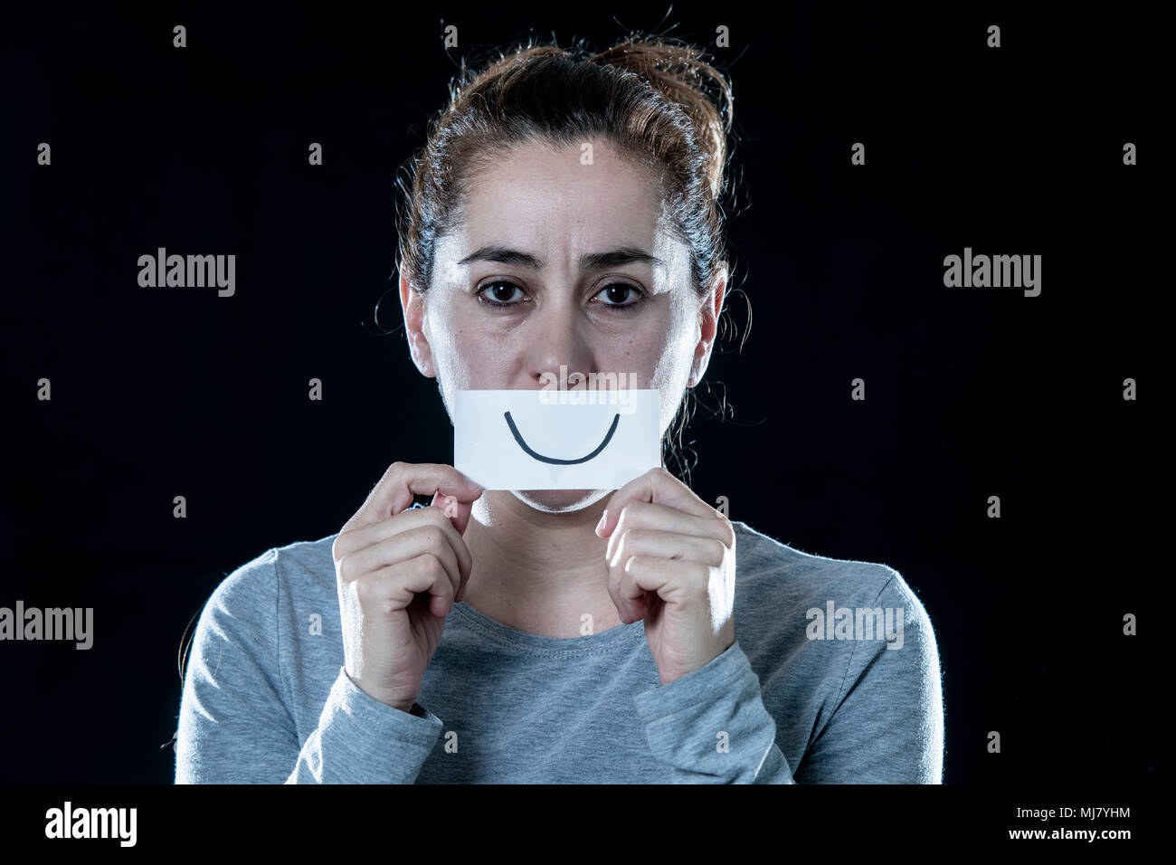 a7bd54421c0 Young beautiful sad and depressed latin woman covering her sad face with a  paper cut out happy face in a depression concept on isolated black backgrou