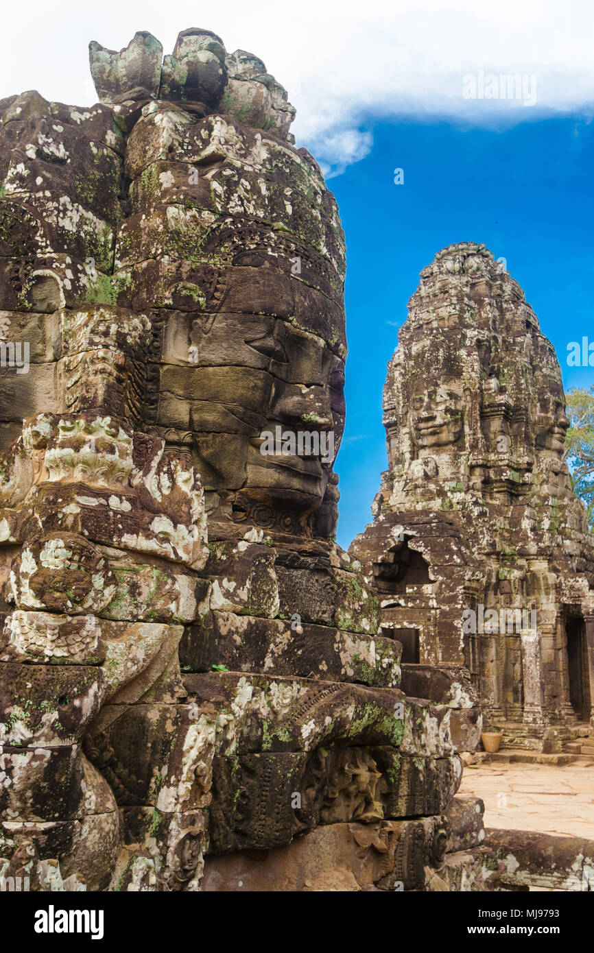 A monumental stone face of the famous Bayon temple in Angkor, Cambodia. In the background, another tower with two face sculptures can be seen. - Stock Image