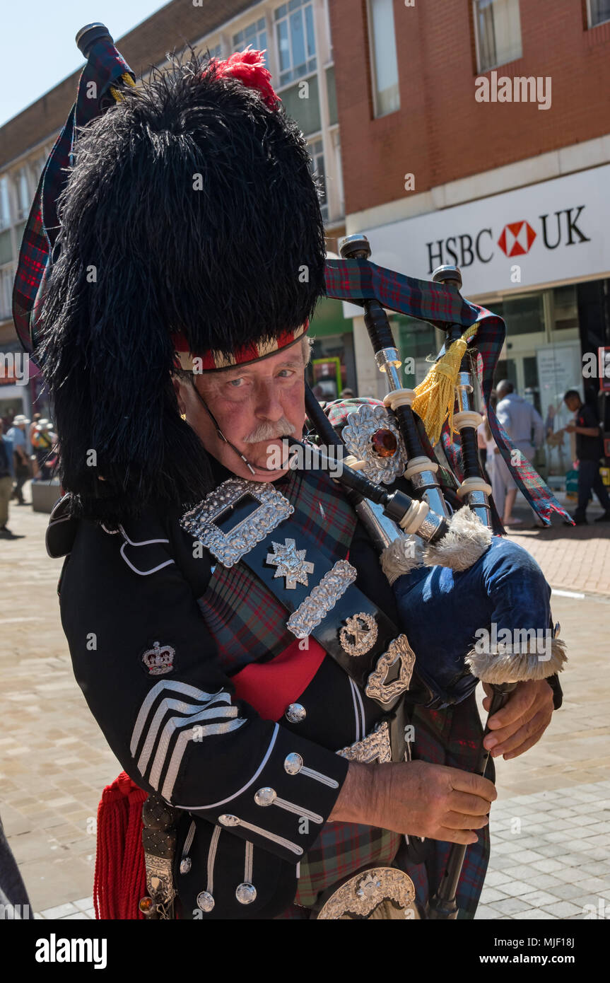 London, UK. 5th March 2018. A piper arrives to lead Trade unionists and other socialistson their march through Croydon town centre to a rally at Ruskin House in celebration of May Day, International Workers Day which is celebrated internationally on May 1st.  Unfortunately May Day is not a Bank Holiday in the UK. The marchers were lead through the main shopping street by a piper and drummer in full Scots dress, attracting the attention of shoppers and others on the busy street. I left the march before it reached Ruskin House where there was to be a rally with speakers including Ted Knight. Pet - Stock Image
