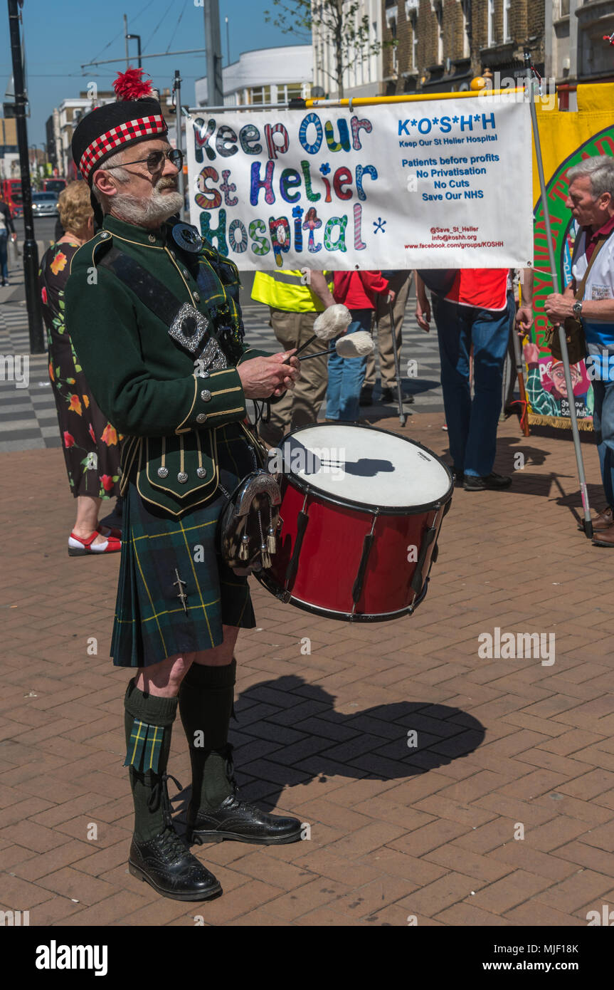 London, UK. 5th March 2018. A drummer gets ready to accompany the piper leading trade unionists and other socialistson their march through Croydon town centre to a rally at Ruskin House in celebration of May Day, International Workers Day which is celebrated internationally on May 1st.  Unfortunately May Day is not a Bank Holiday in the UK. The marchers were lead through the main shopping street by a piper and drummer in full Scots dress, attracting the attention of shoppers and others on the busy street. I left the march before it reached Ruskin House where there was to be a rally with speake - Stock Image