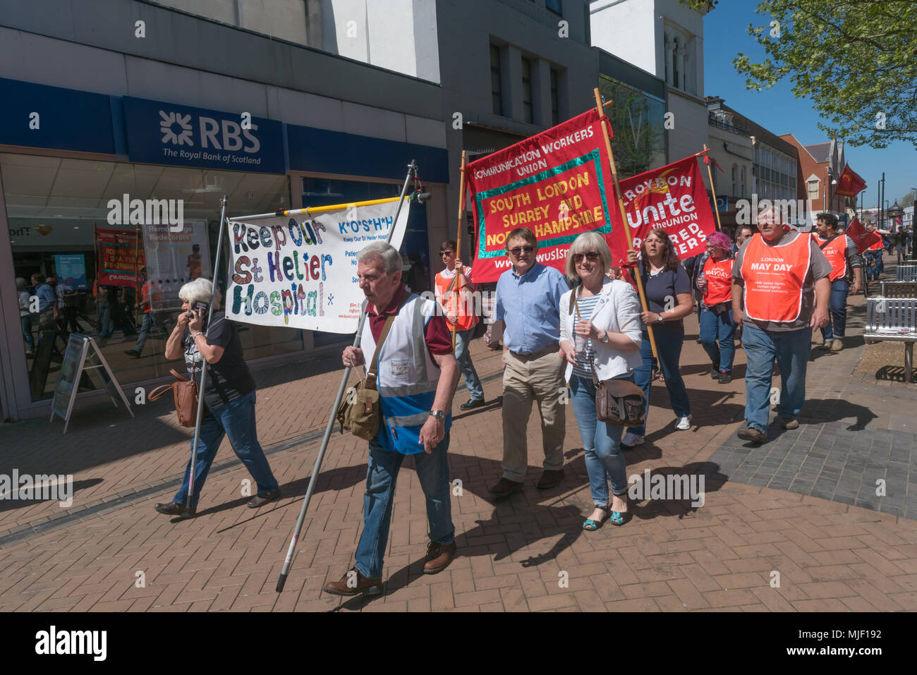 London, UK. 5th March 2018. Trade unionists and other socialists with posters and banners on the march through Croydon town centre to a rally at Ruskin House in celebration of May Day, International Workers Day which is celebrated internationally on May 1st.  Unfortunately May Day is not a Bank Holiday in the UK. The marchers were lead through the main shopping street by a piper and drummer in full Scots dress, attracting the attention of shoppers and others on the busy street. I left the march before it reached Ruskin House where there was to be a rally with speakers including Ted Knight. Pet Stock Photo