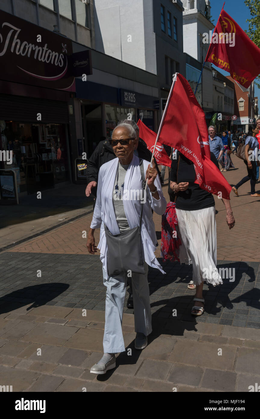 London, UK. 5th March 2018.  Ellen Lebethe, chair of Lambeth pensioners action group holds a Unite flags as trade unionists and other socialists march through Croydon town centre to a rally at Ruskin House in celebration of May Day, International Workers Day which is celebrated internationally on May 1st.  Unfortunately May Day is not a Bank Holiday in the UK. The marchers were lead through the main shopping street by a piper and drummer in full Scots dress, attracting the attention of shoppers and others on the busy street. I left the march before it reached Ruskin House where there was to be - Stock Image