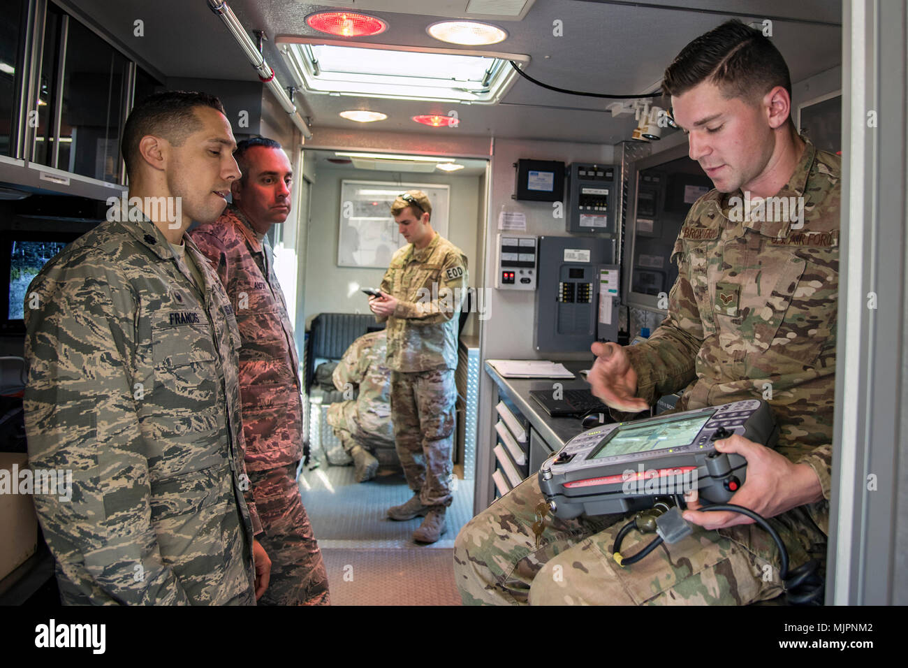 Senior Airman Trenton Broxterman, 23d Civil Engineer Squadron (CES) Explosive Ordinance Disposal (EOD) apprentice, explains a display screen to Lt. Col Michael Francis, 23d CES commander, during a response training exercise, Dec 21, 2017, at Moody Air Force Base, Ga. The EOD Airmen were evaluated on their ability to respond to a distress call, locate, identify and neutralize an improvised explosive device. (U.S. Air Force photo by Airman Eugene Oliver) - Stock Image