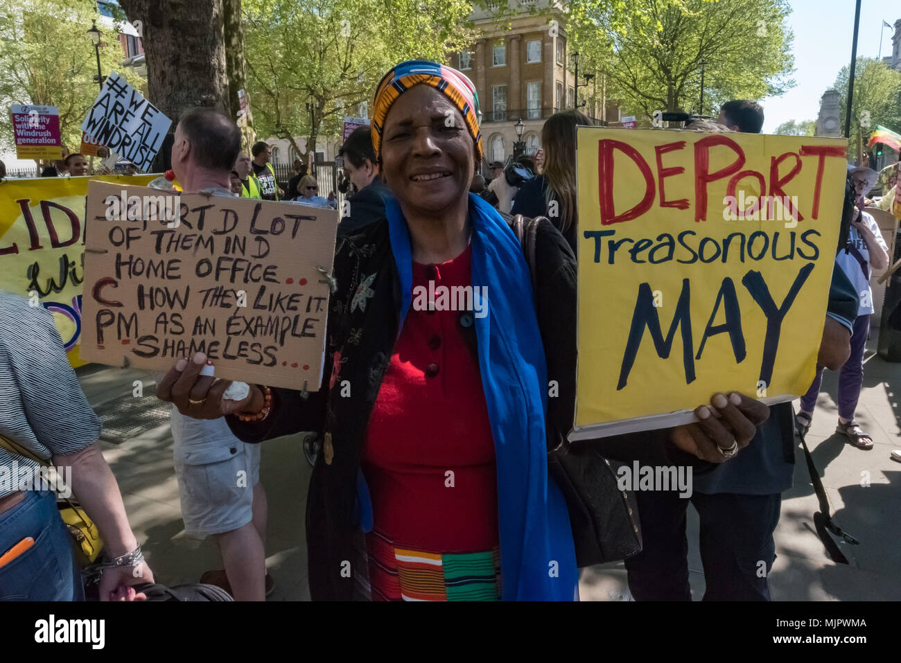 London, UK. 5th May 2018.A woman holds posters calling for Theresa May and the Home  Office staff to be deported at the Stand Up To Racism rally at Downing St calling for Theresa May's racist 2014 Immigration Act to be repealed and an immediate end to the deportation and detention of Commonwealth citizens, with those already deported to be bought back to the UK. The protesters called for protection to the guaranteed for all Commonwealth citizens and for those affected to be compensated for deportation, threats of deportation, detention, loss of housing, jobs, benefits and denial of NHS treatme - Stock Image