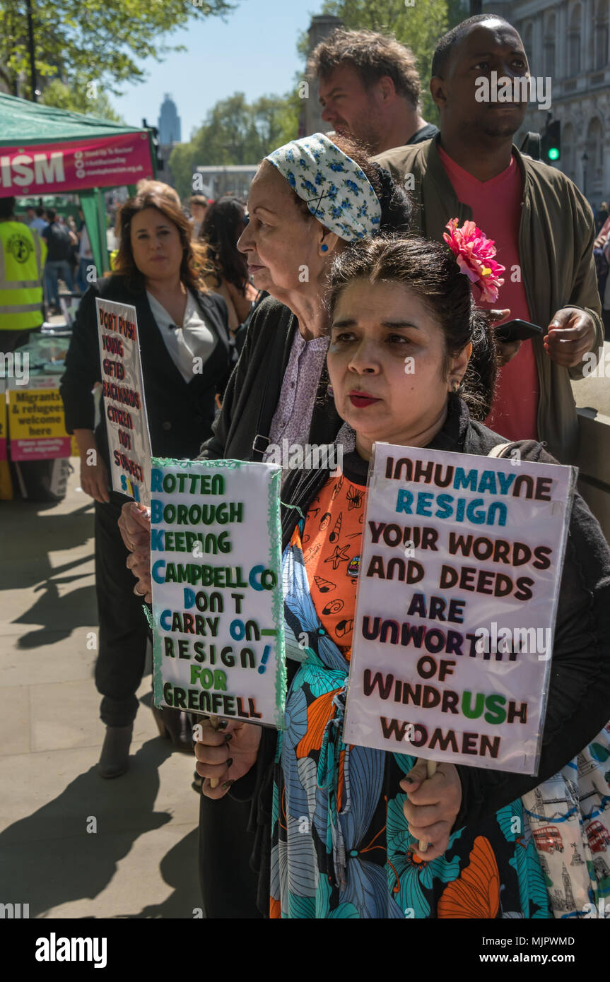 London, UK. 5th May 2018. A woman who worked in Grenfell Tower holds up posters against the Kensington & Chelsea Council leader and Theresa May to resign at the Stand Up To Racism rally at Downing St calling for Theresa May's racist 2014 Immigration Act to be repealed and an immediate end to the deportation and detention of Commonwealth citizens, with those already deported to be bought back to the UK. The protesters called for protection to the guaranteed for all Commonwealth citizens and for those affected to be compensated for deportation, threats of deportation, detention, loss of housing, - Stock Image