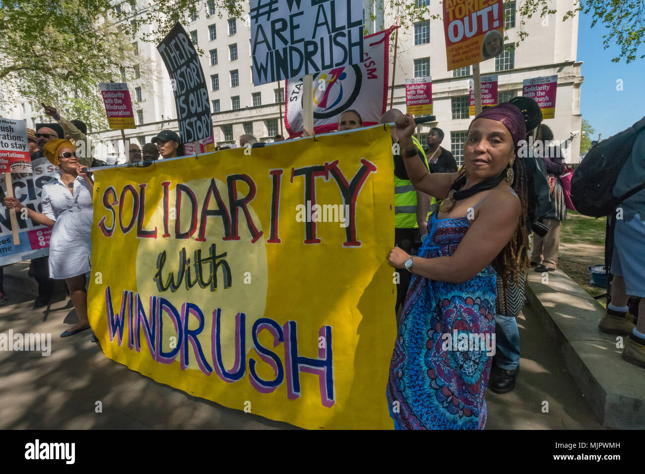London, UK. 5th May 2018. People hold the 'Solidarity With Windrush' banner at the Stand Up To Racism rally at Downing St calling for Theresa May's racist 2014 Immigration Act to be repealed and an immediate end to the deportation and detention of Commonwealth citizens, with those already deported to be bought back to the UK. The protesters called for protection to the guaranteed for all Commonwealth citizens and for those affected to be compensated for deportation, threats of deportation, detention, loss of housing, jobs, benefits and denial of NHS treatment. There should be an end to the 'ho - Stock Image