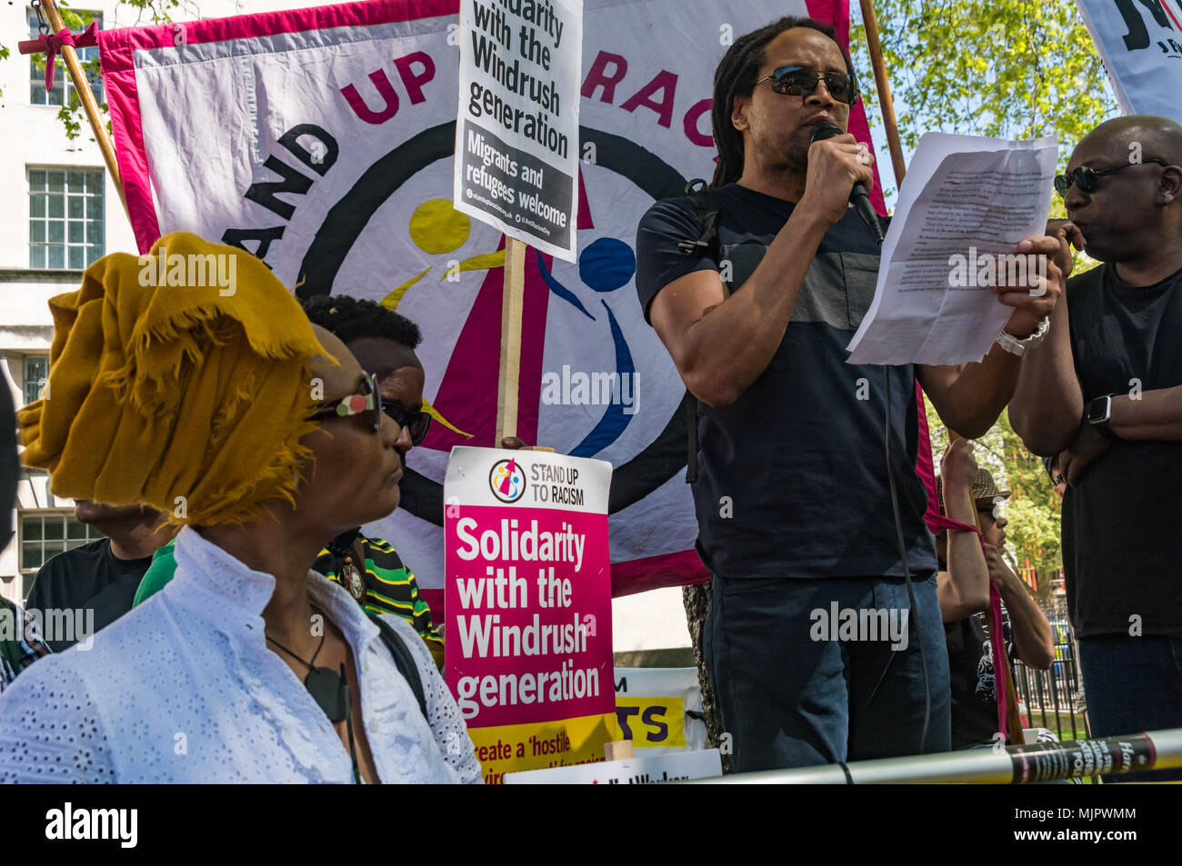 London, UK. 5th May 2018. A speaker at the Stand Up To Racism rally at Downing St calling for Theresa May's racist 2014 Immigration Act to be repealed and an immediate end to the deportation and detention of Commonwealth citizens, with those already deported to be bought back to the UK. The protesters called for protection to the guaranteed for all Commonwealth citizens and for those affected to be compensated for deportation, threats of deportation, detention, loss of housing, jobs, benefits and denial of NHS treatment. There should be an end to the 'hostile environment' for all immigrants. S - Stock Image