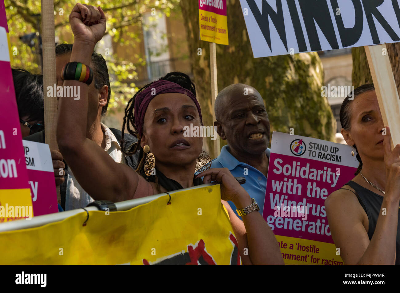 London, UK. 5th May 2018. A woman raises her fist at the Stand Up To Racism rally at Downing St calling for Theresa May's racist 2014 Immigration Act to be repealed and an immediate end to the deportation and detention of Commonwealth citizens, with those already deported to be bought back to the UK. The protesters called for protection to the guaranteed for all Commonwealth citizens and for those affected to be compensated for deportation, threats of deportation, detention, loss of housing, jobs, benefits and denial of NHS treatment. There should be an end to the 'hostile environment' for all - Stock Image