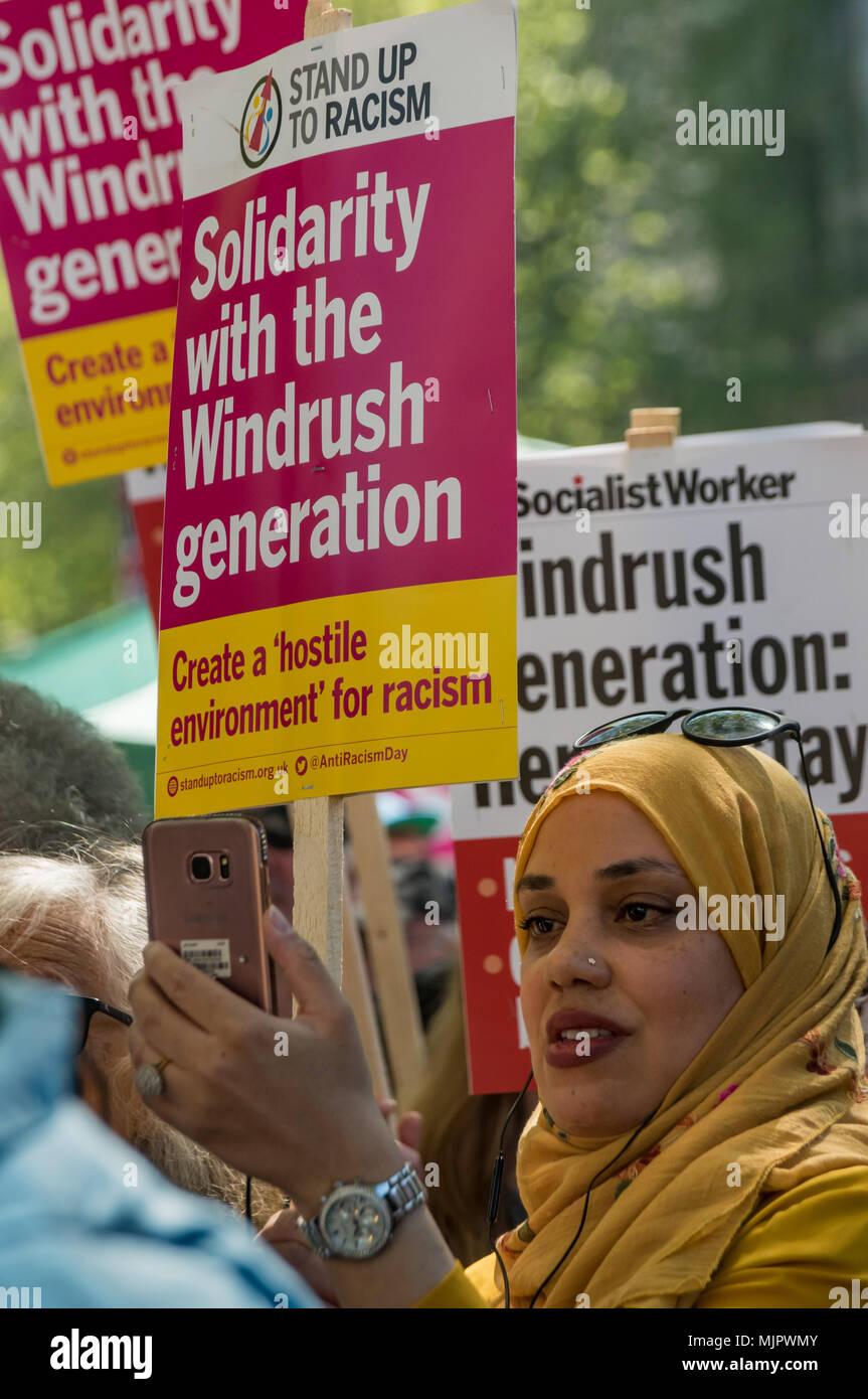 London, UK. 5th May 2018. A woman films with her phone at the Stand Up To Racism rally at Downing St calling for Theresa May's racist 2014 Immigration Act to be repealed and an immediate end to the deportation and detention of Commonwealth citizens, with those already deported to be bought back to the UK. The protesters called for protection to the guaranteed for all Commonwealth citizens and for those affected to be compensated for deportation, threats of deportation, detention, loss of housing, jobs, benefits and denial of NHS treatment. There should be an end to the 'hostile environment' fo - Stock Image