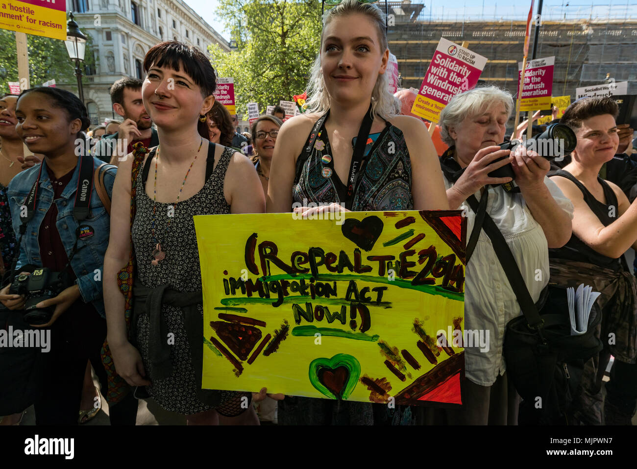 London, UK. 5th May 2018. A woman holds a poster 'Repeal the 2014 Immigration Act Now!' at the Stand Up To Racism rally at Downing St calling for Theresa May's racist 2014 Immigration Act to be repealed and an immediate end to the deportation and detention of Commonwealth citizens, with those already deported to be bought back to the UK. The protesters called for protection to the guaranteed for all Commonwealth citizens and for those affected to be compensated for deportation, threats of deportation, detention, loss of housing, jobs, benefits and denial of NHS treatment. There should be an en - Stock Image