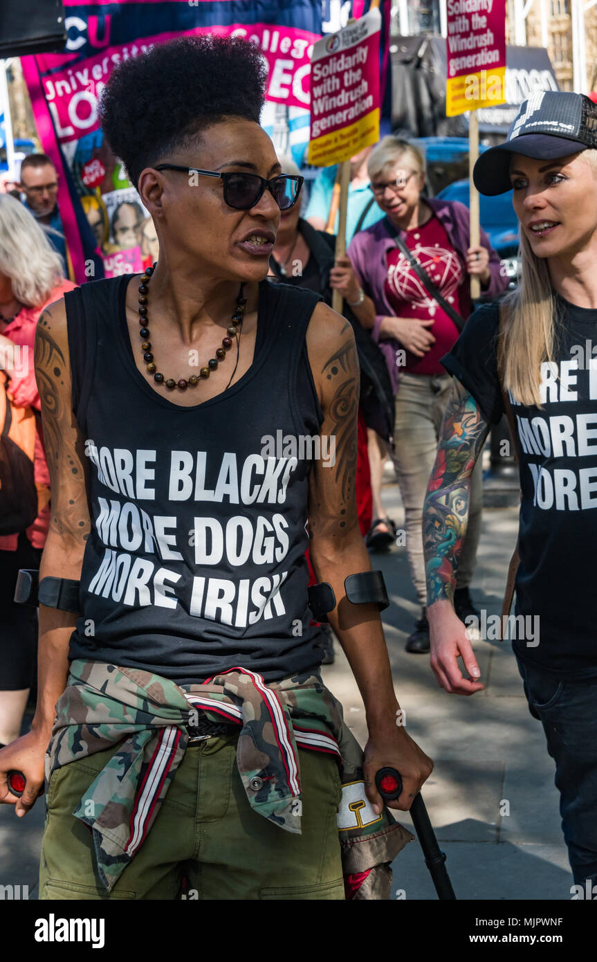 London, UK. 5th May 2018. A woman wearing a t-shirt 'More Blacks More Dogs More Irish' marches with the help of crutches from Downing St for a protest outside the Home Office calling for Theresa May's racist 2014 Immigration Act to be repealed and an immediate end to the deportation and detention of Commonwealth citizens, with those already deported to be bought back to the UK. They called for protection to the guaranteed for all Commonwealth citizens and for those affected to be compensated for deportation, threats of deportation, detention, loss of housing, jobs, benefits and denial of NHS t - Stock Image