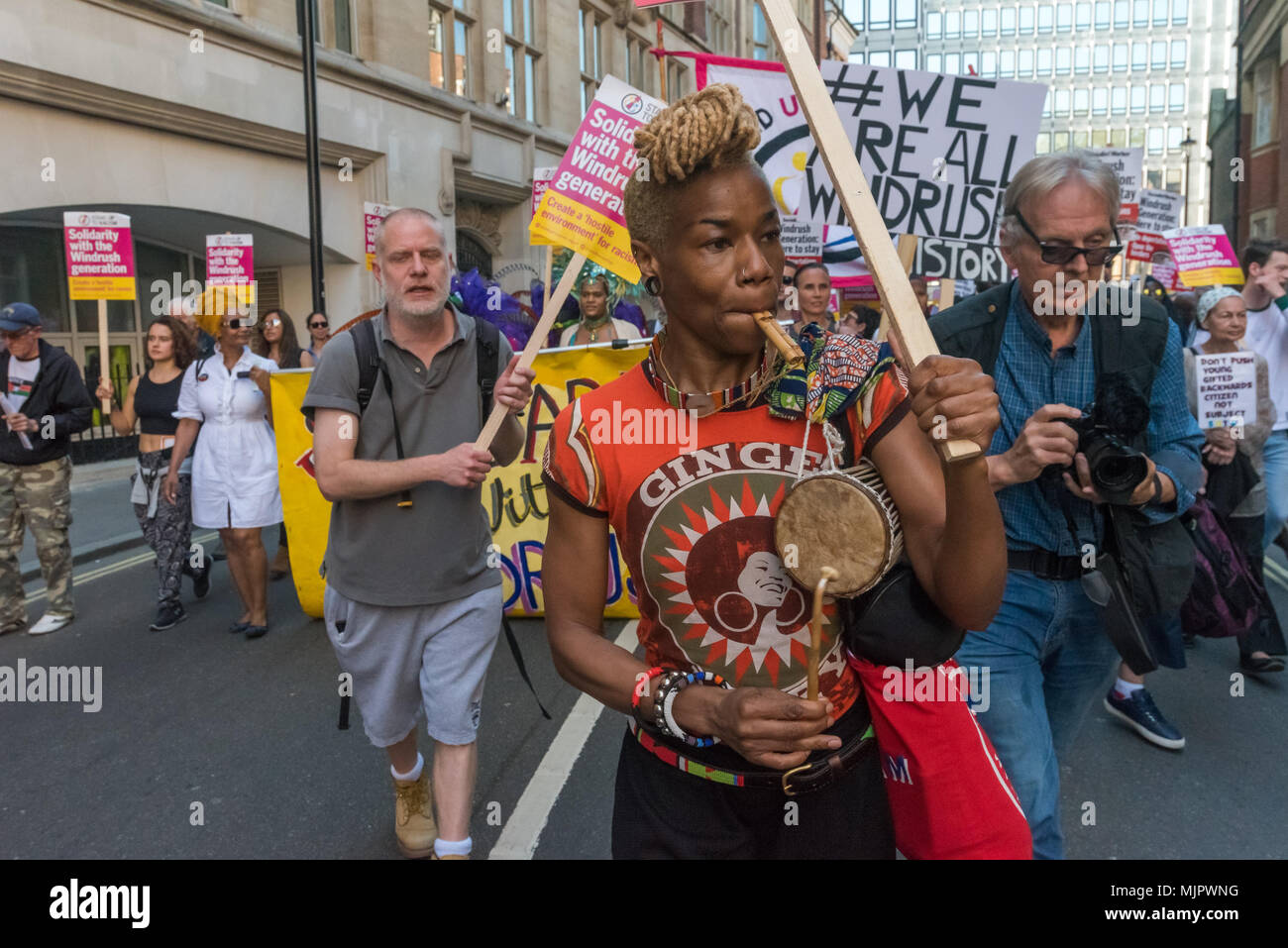 London, UK. 5th May 2018. A woman blows a whistel , beats a drum and holds a placard as she marches from the a rally at Downing St to protest outside the Home Office calling for Theresa May's racist 2014 Immigration Act to be repealed and an immediate end to the deportation and detention of Commonwealth citizens, with those already deported to be bought back to the UK. They called for protection to the guaranteed for all Commonwealth citizens and for those affected to be compensated for deportation, threats of deportation, detention, loss of housing, jobs, benefits and denial of NHS treatment. - Stock Image