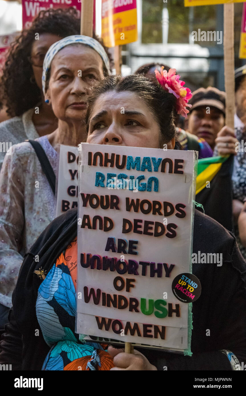 London, UK. 5th May 2018. A woman who worked in the nursery at Grenfell Tower holds a poster calling on Theresa May to resing at the protest outside the Home Office calling for Theresa May's racist 2014 Immigration Act to be repealed and an immediate end to the deportation and detention of Commonwealth citizens, with those already deported to be bought back to the UK. They called for protection to the guaranteed for all Commonwealth citizens and for those affected to be compensated for deportation, threats of deportation, detention, loss of housing, jobs, benefits and denial of NHS treatment.  - Stock Image