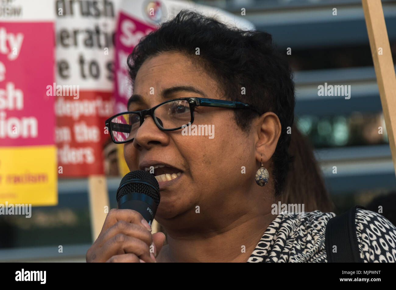 London, UK. 5th May 2018. An immigration lawyer reads a poem she has written about the Windrush experience of arriving in cold damp England and experiencing raciism at the protest outside the Home Office calling for Theresa May's racist 2014 Immigration Act to be repealed and an immediate end to the deportation and detention of Commonwealth citizens, with those already deported to be bought back to the UK. They called for protection to the guaranteed for all Commonwealth citizens and for those affected to be compensated for deportation, threats of deportation, detention, loss of housing, jobs, - Stock Image