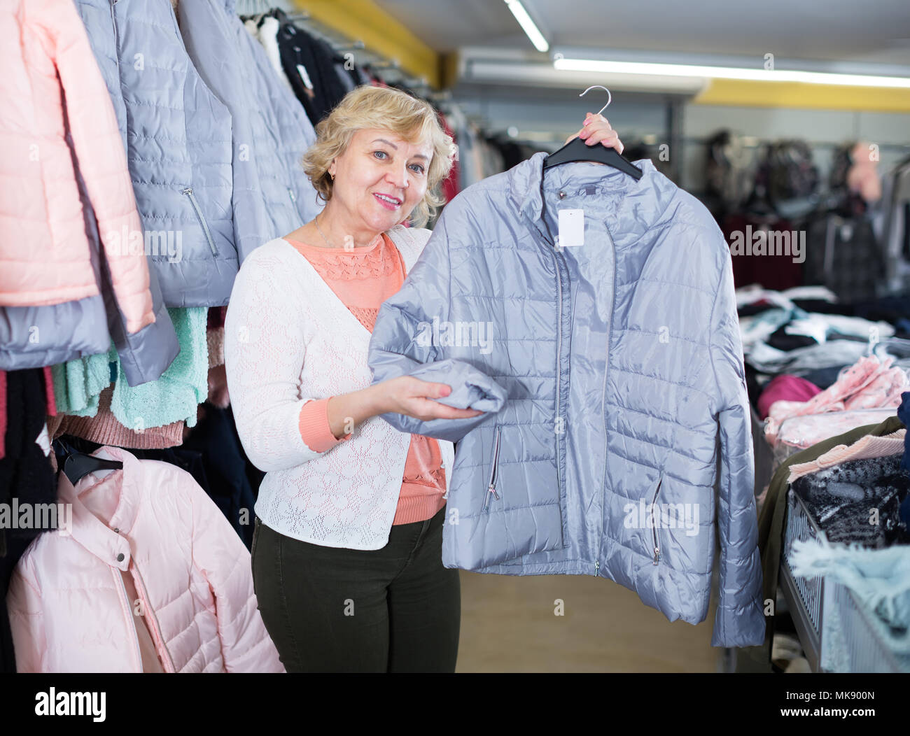 Adult female purchaser choosing windbreaker jackets in the shopping center - Stock Image